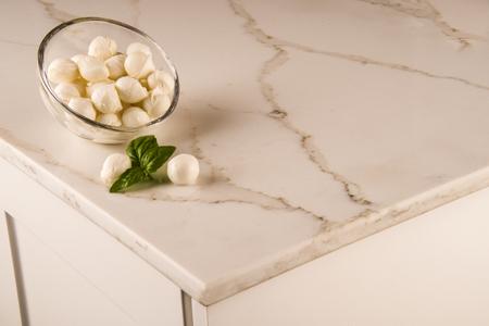 White elegant kitchen marble counter top with italian mozzarela on it, white kitchen cabinets Stockfoto
