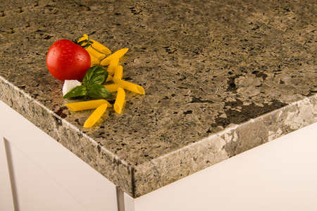 granite kitchen: White kitchen cabinets with greenish granite countertop with food decoration on