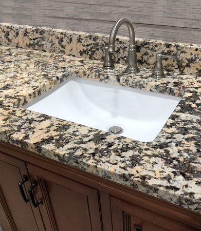 Bathroom vanity granite countertop made of natural stone with rectangular white sink and chrome faucet
