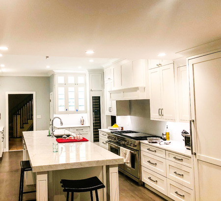 Modern white kitchen cabinets with a stainless steel appliances and island with white marble countertop and under mount sink