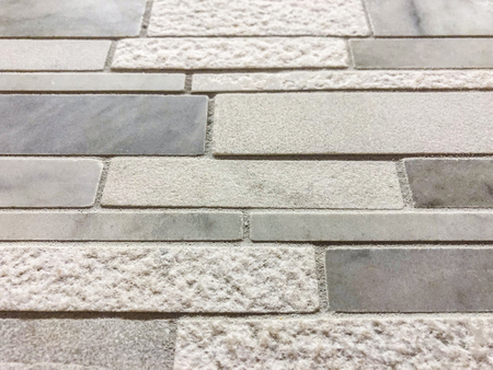 Gray rectangular tile of different texture and stones plased horizontaly,can be used as wall or floor tile or kitchen countertop backsplash