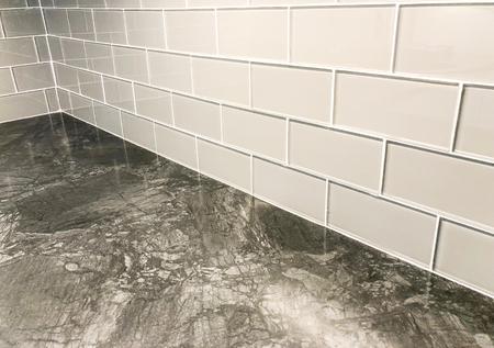 Encimera gris con placa para salpicaduras de azulejos blancos enchapada horizontalmente en unión de camilla, se puede usar como azulejo de piso o azulejo de pared