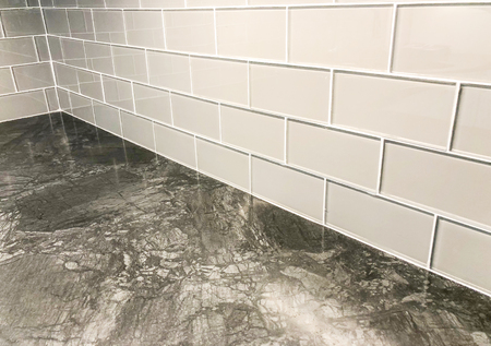 Graue Arbeitsplatte mit weißer Fliesenrückwand horizontal im Keilrahmen plattiert, kann als Bodenfliese oder Wandfliese verwendet werden