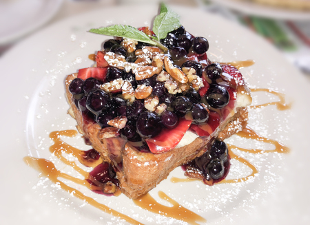 Breakfast French toast with strawberries, berries, walnuts and dripping maple syrup and mint leaves on white plate. Stock Photo