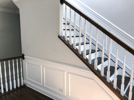 White stairway made of wood panels, wide house stairs View of stairs with white rail.