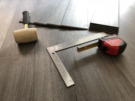 Luxury flooring concept. Vinyl plank laminate floor. Worker preparing for new floor installation.