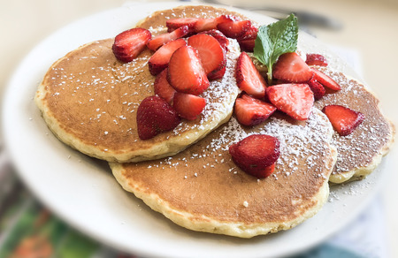 Pancakes topped with strawberry, mint and powder. Breakfast concept Imagens