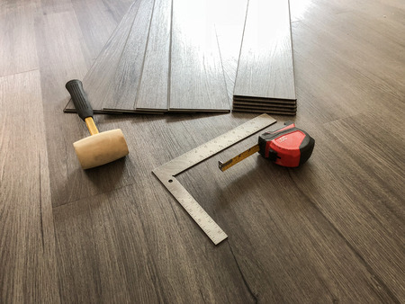 Luxury flooring concept. Vinyl plank laminate floor. Worker preparing for new floor installation.