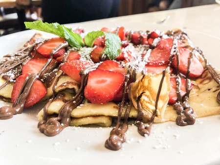 Crepes with chocolate spread and hazelnuts. Homemade thin crepes for breakfast or dessert on white, copy space. Stock Photo