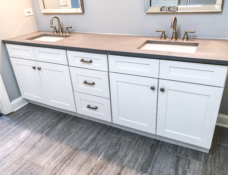 White cabinets with counter in bathroom, two china sinks, faucets, mirrors amd gray floor tiles.