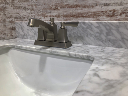 marble countertop on bathroom vanity with chrome faucet and decorative wall backsplash
