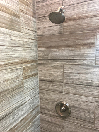 bathroom shower with beautiful decorative stone tiles shower head and shower handle in chrome