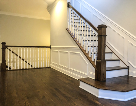 Stairs of the luxury house with white walls, wood panels in white color, dark cherry hardwood floor Stock Photo