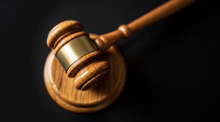 judge or auction Gavel on a wood block in courtroom, dark background