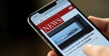 Online news on a smart phone. Businessman reading news or article on a mobile phone screen app. Hand holding smart device. Newspaper and portal on internet. Displayed news are not reality related.