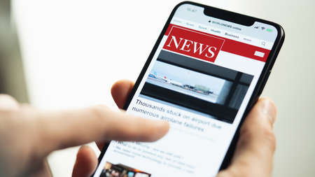 Online news on a smart phone. Businessman reading news or article on a mobile phone screen app. Hand holding smart device. Newspaper and portal on internet. Displayed news are not reality related. Redactioneel