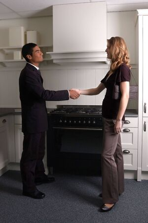 inquiries: Young woman talking with a sales representative to buy a kitchen in a kitchenstore.