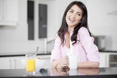 Young woman in kitchen enjoying some orange juice and fresh fruit