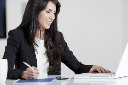 Young woman working at her desk in the office Stock Photo - 13985152