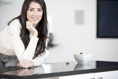 Young woman enyoying a bowl of fresh fruit in her kitchen Stock Photo