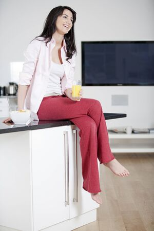 Young woman sitting on counter drinking orange juice Stock Photo
