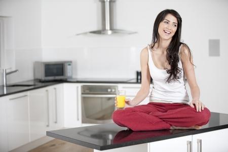 bondad: Joven mujer sentada en contra de beber el jugo de naranja Foto de archivo