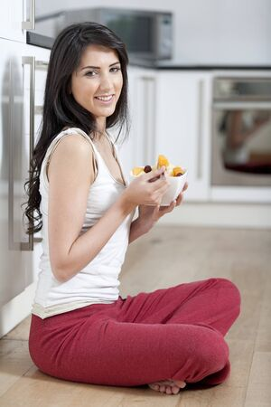 Young woman enjoying a bowl of fresh fruit in her kitchen
