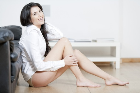 Young woman leaning against sofa in underwear