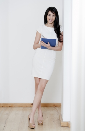 Young woman in white dress leaning against a white wall holding a blue folder photo