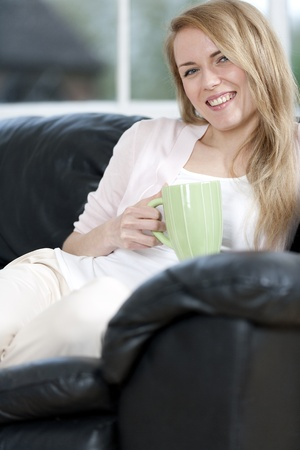 Young woman enjoying a hot drink at home on the sofa Stock Photo - 14015923