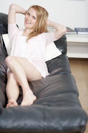 Young woman lying on sofa at home Stock Photo - 14015827