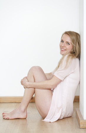 Young woman at home in underwear and pink shirt smiling
