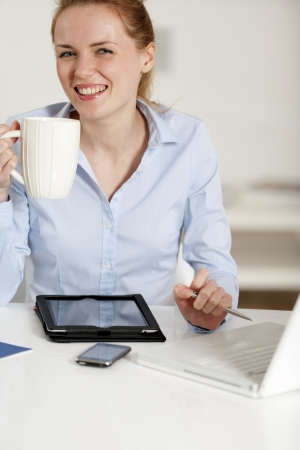 Young woman working at her desk in the office Stock Photo - 14015762
