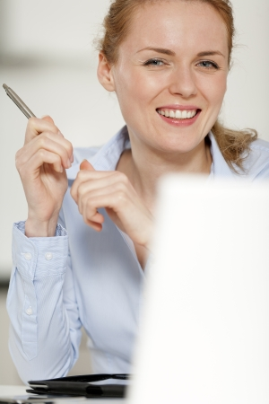 Young woman working at her desk in the office Stock Photo - 14015829