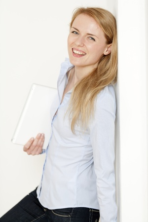 Young woman leaning against a white wall holding a white laptop computer Stock Photo