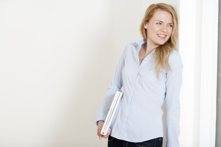 Young woman leaning against a white wall holding a white laptop computer photo