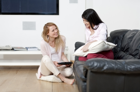 Two woman in their sitting room chatting and having fun on an electronic tablet Stock Photo