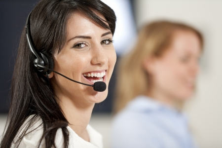 Two colleagues working in a busy call centre office. Stock Photo