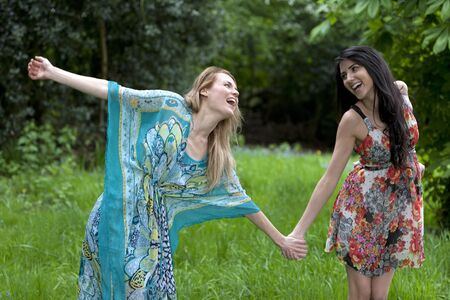 Two friends messing around in a field in summer time Stock Photo