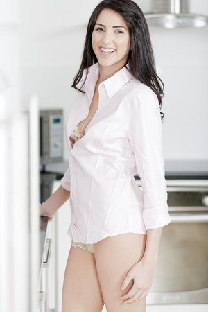 Young woman in underwear and pink shirt stood in kitchen
