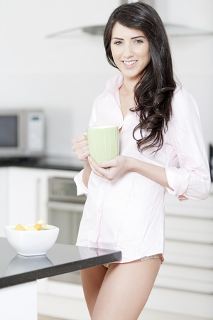 Young woman in underwear and pink shirt stood in kitchen eating breakfast Stock Photo