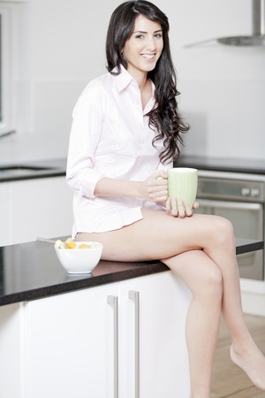 Young woman in underwear and pink shirt sat in kitchen eating breakfast Stock Photo