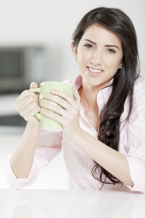 Young woman in pink shirt sitting at dining table at home drinking a hot drink. photo