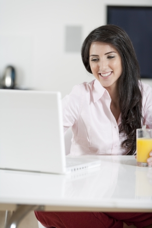 Girl using laptop at home to chat with friends photo