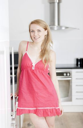 Young woman wearing pink knighty in kitchen Stock Photo
