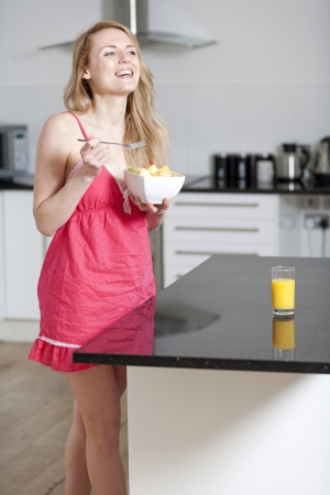 Young woman wearing pink knighty in kitchen eating breakfast