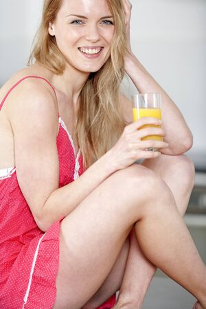 Young woman wearing pink knighty in kitchen drinking fresh orange juice