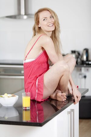Young woman wearing pink knighty in kitchen with her breakfast. Stock Photo
