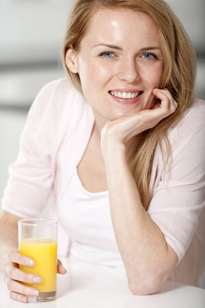 Young woman in pink shirt sitting at dining table at home with orange juice photo