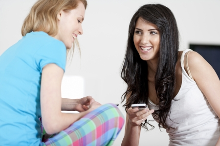 Two young woman chatting and using their mobile phones at home Stock Photo